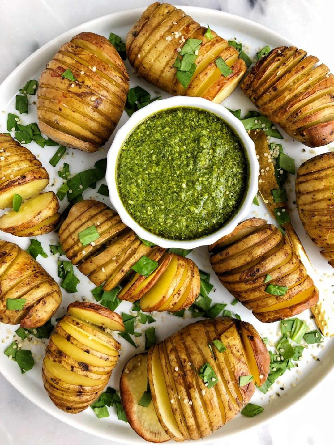 Sharing these Whole30 Hasselback Potatoes with Garlicky Basil Pesto. Extra crispy potatoes paired with the dreamiest dairy-free pesto. A delicious vegan Whole30 recipe!
