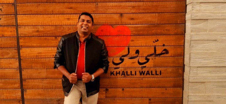Savio Fernandes, an Indian man stands in front of a brick wall smiling. The brick wall has a heart painted along with Arabic words, 'Khalli Walli' written on it.