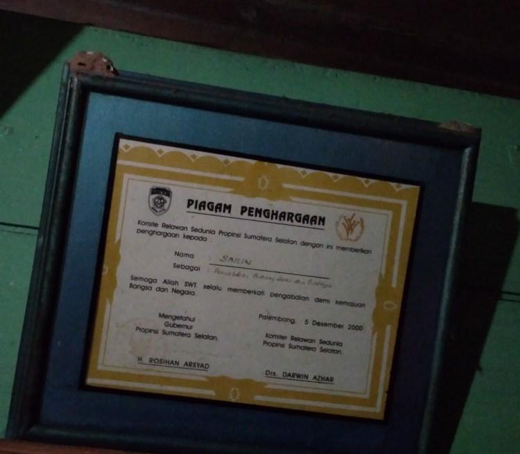 Penghargaan yang diberikan oleh Komite Relawan Sedunia kepada Bapak Sahilin, terlihat terdapat sarang rayap di bagian kiri atas.