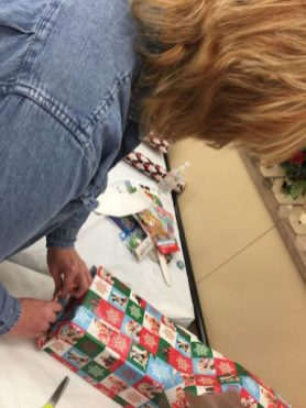 Beth David puts the finishing touch on a gift box for Santa in a Shoebox. Photo credit: Heather Asiyanbi