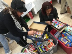 Santa in a Shoebox Racine Founder Diana Anderson Higgenbottom (left) chooses items from one of several totes filled with goodies. Photo credit: Heather Asiyanbi