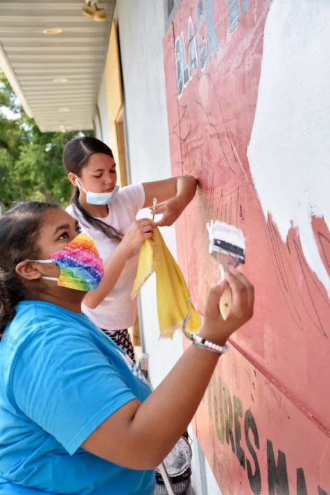 Malika Robinson, right, and Marciara Fuller, both 15 and of Kenosha, work on a mural on the east side of the building that houses Diver Dan's Scuba and Aquatic at 3927 30th Ave. in Kenosha on Sept. 3, 2020. Photo by Daniel Thompson/The Uptown Observer