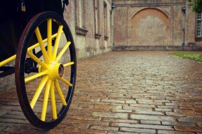 yellow carriage wheel on cobblestone
