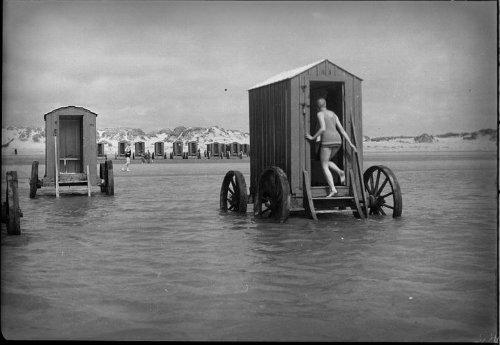 Woman climbs into bathing machine.