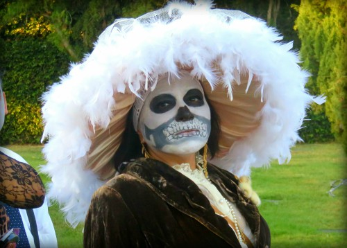Catrina Skull makeup in coloredphoto of woman neck up with bell shaped white feather hat at Los Angeles Hollywood Cemetery, Day of the Dead. Image: B. Rose Media.