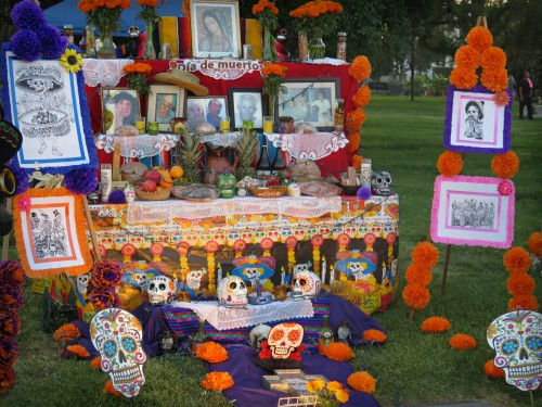 Catrina Skull altar with marigolds and multiple photos in colorful frames atLos Angeles Hollywood Cemetery, Day of the Dead Altar. Image: B. Rose Media.