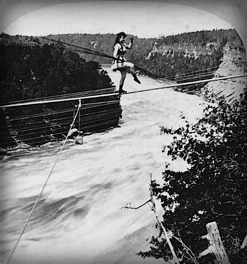 Maria Spelterini on tight rope across Niagara falls while holding horizontal balance stick.
