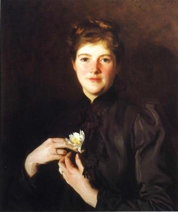 portrait of Harriet Lawrence Hemenway in dark dress with dark background holding flower in both hands