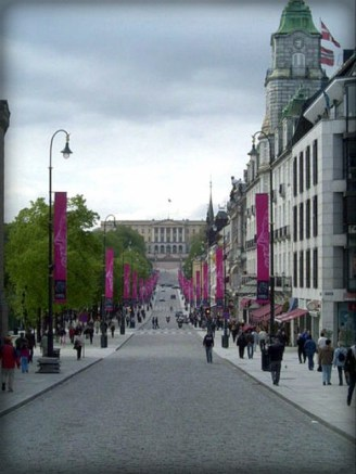 Karl Johans Street, Oslo, Norway. lined with long purple banners, trees and people walking Image: Wikivisually