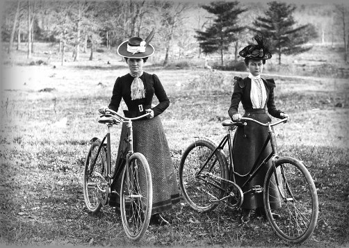 black and white photo of two women 1900 in long dresses with bikes and victorian bicycle face