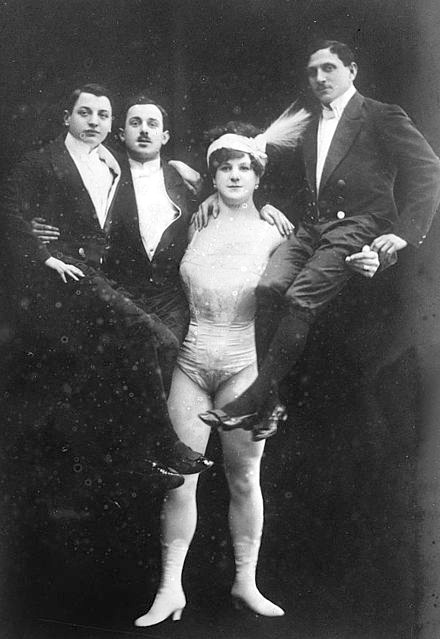 Victorian Strongwomen Sandwina holds three men in a black and white photo, early 1900s.