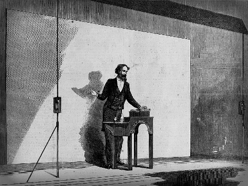 Illustration of Charles Dickens, Public Reading with reading table and prop book, 1867. Image: Wikipedia.