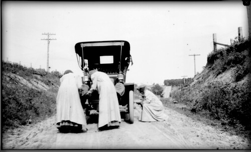 Three women in long victorian dresses fixing 1905 automobile,