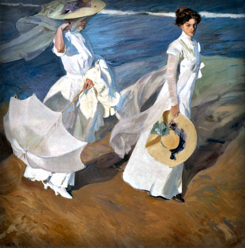 Painting of two women in long white dresses and large straw hats strolling along the seashore in 1909