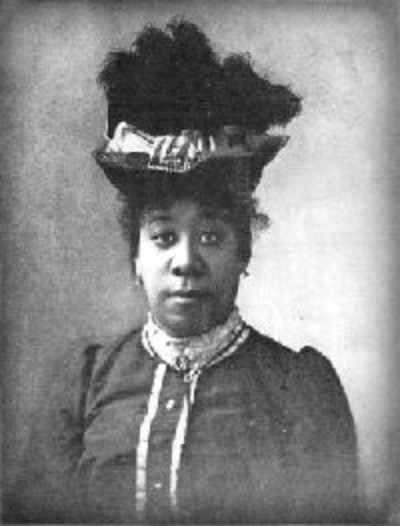 black and white photo, bust and head of African American woman Pauline Hopkins in Victorian dress with feathered hat
