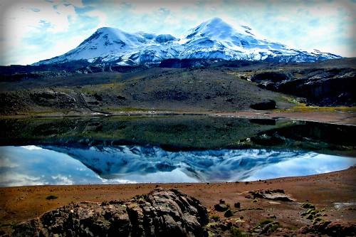 Coropuna Volcano, double peak reflected in a lake below. Image: Wikipedia.