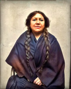 Waist up, seated photograph of Mary Baldwin Bottineau, 1914 in braids and Native American robe. Image: Library of Congress.
