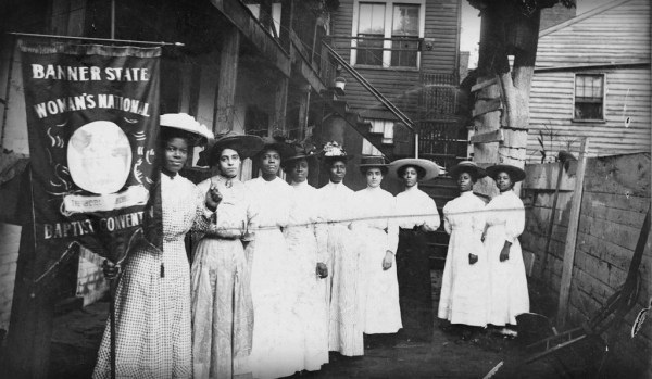 Nine African American Women in White Victorian Dresses and Hats and one up front holds Women's rights Banner.