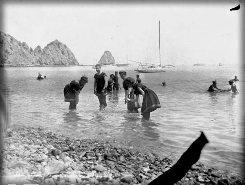 Victorian Era Catalina photo of six people knee deep in ocean with sugar loaf rock in backgroundSwimmers, 1900. Image: WaterAnd Power.org.