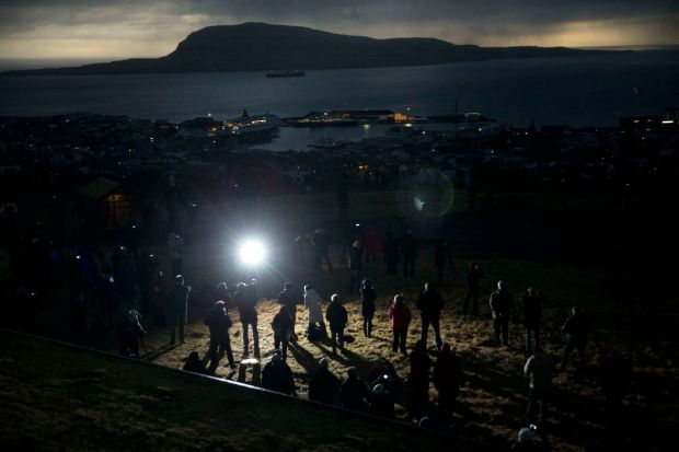 People watch in darkness during the totality of a solar eclipse on as seen from a hill beside a hotel on the edge of the city overlooking Torshavn, the capital city of the Faroe Islands.