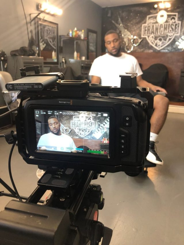 A behind-the-camera shot of a Black man being interviewed.