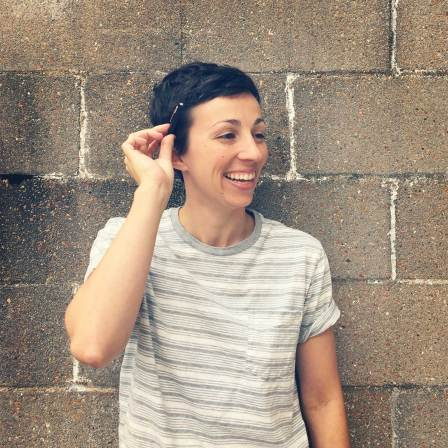 Photo of the artist Jenny Murphy in front of a concrete brick wall