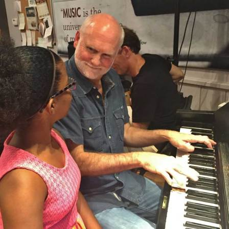 An older man sits at a piano, teaching piano to a young girl.