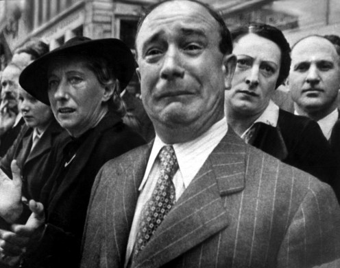 A frenchman weeps as german soldiers march into Paris