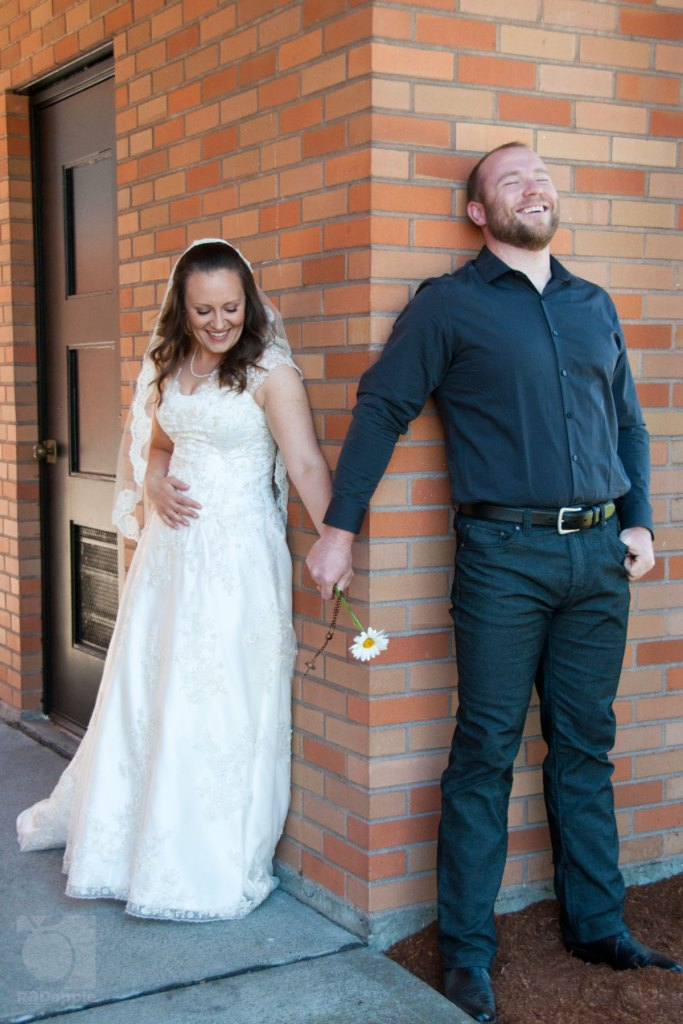 Bride and groom on different sides of building holding hands