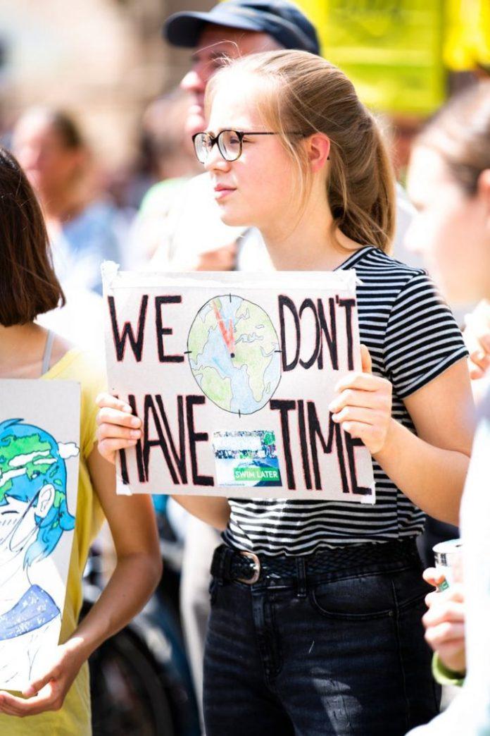 """Instituição reconhece necessidade de reposicionamento das lideranças globais para atender as demandas da sociedade. Foto por Markus Spiske temporausch.com em <a href=""""https://www.pexels.com/photo/woman-holding-we-don-t-have-time-signage-2559747/"""" rel=""""nofollow"""">Pexels.com</a>"""