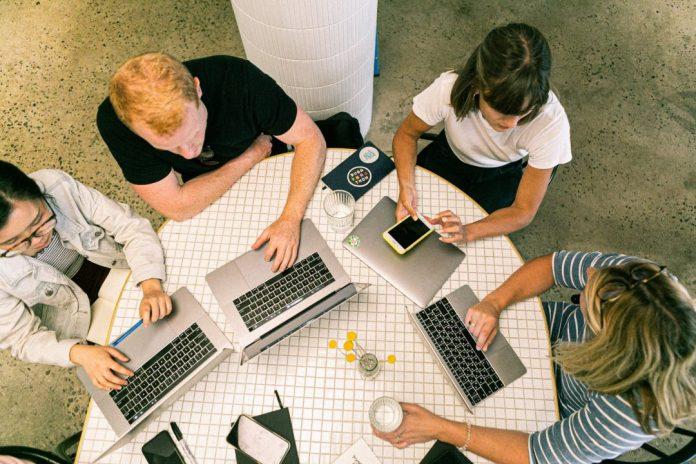 Reunião de quatro pessoas em torno de uma mesa, cada um com seu notebook. Foto por Canva Studio em Pexels.com