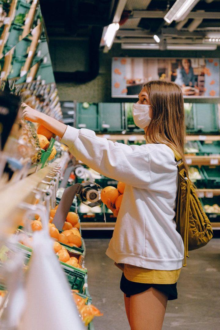 Moça usando máscara em banca de frutas. De acordo com a consultoria Kearney, alimentação, cuidados com pets e beleza & cuidados pessoais são segmentos que registrarão maiores crescimentos percentuais entre 2020 e 2024 Photo by Anna Shvets on Pexels.com