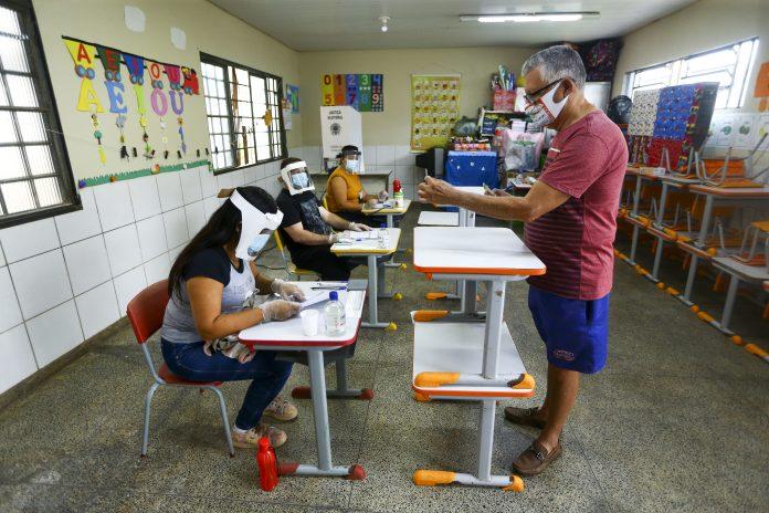 Eleitor mostra documento à distância para mesária das eleições =Marcelo Camargo/Agência Brasil