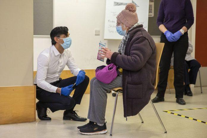 médico conversa com paciente na fila da vacinação do reino unido. foto: Fotos públicas