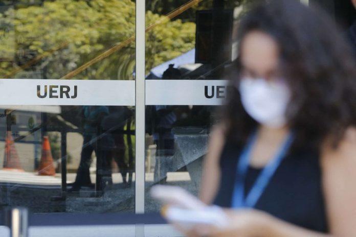 Destaque das notas econômicas:  foto de portaria da UFRJ com destaque para imagem de mulher olhando celuar