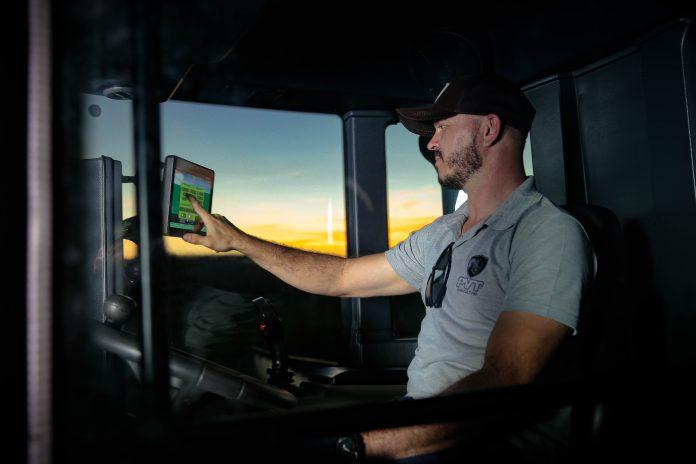 homem dirigindo máquina agrícola consulta tela de minicomputador  potencial do agronegócio