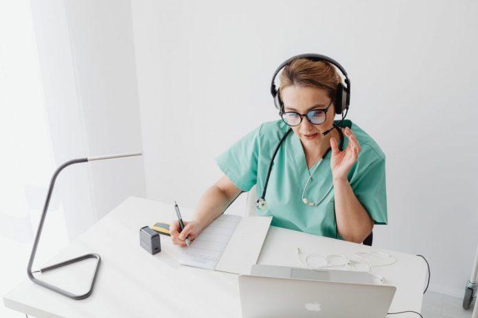 woman taking notes while on video call foto ilustrativa: médica anota enquanto faz anotações em uma videoconversa Assunto: diagnóstico médico
