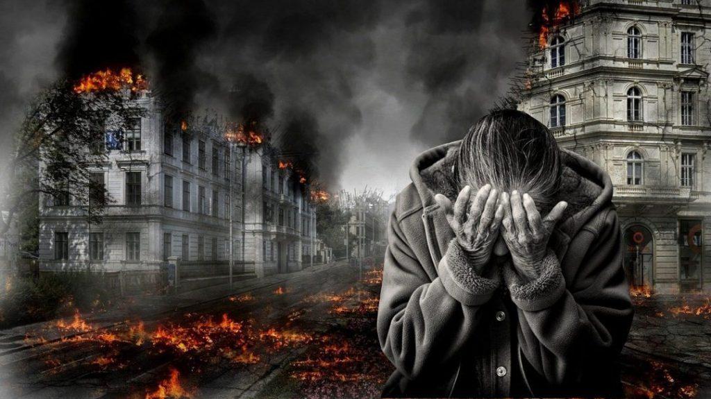 Mulher chora de costas para uma cidade destruída Quer ser um futurista e entender o futuro da humanidade? Leve em conta que os avanços tecnológicos tendem a ser mais rápidos que os civilizatórios.