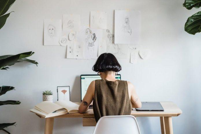 focused female artist working on laptop in light room Templatetização é tendência no futuro do desenvolvimento de soluções digitais. Conhecer o conceito proposto é um dos assuntos das conversas sobre o futuro