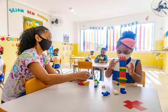 foto para matéria sobre futuro da educação. Professora e aluna dentro da sala de aula, com máscara, montam um brinquedo