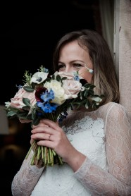 Bride holding her bouquet and smiling at Askham Hall