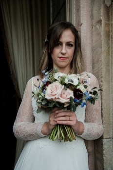 Bride looking over her bouquet at Askham Hall, Cumbria