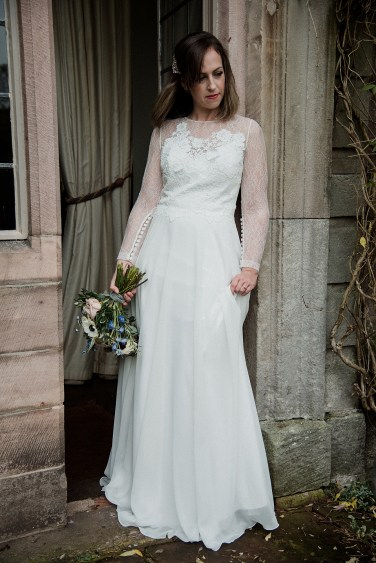 Bridal holding her dress and flowers at Askham Hall, Eden Valley