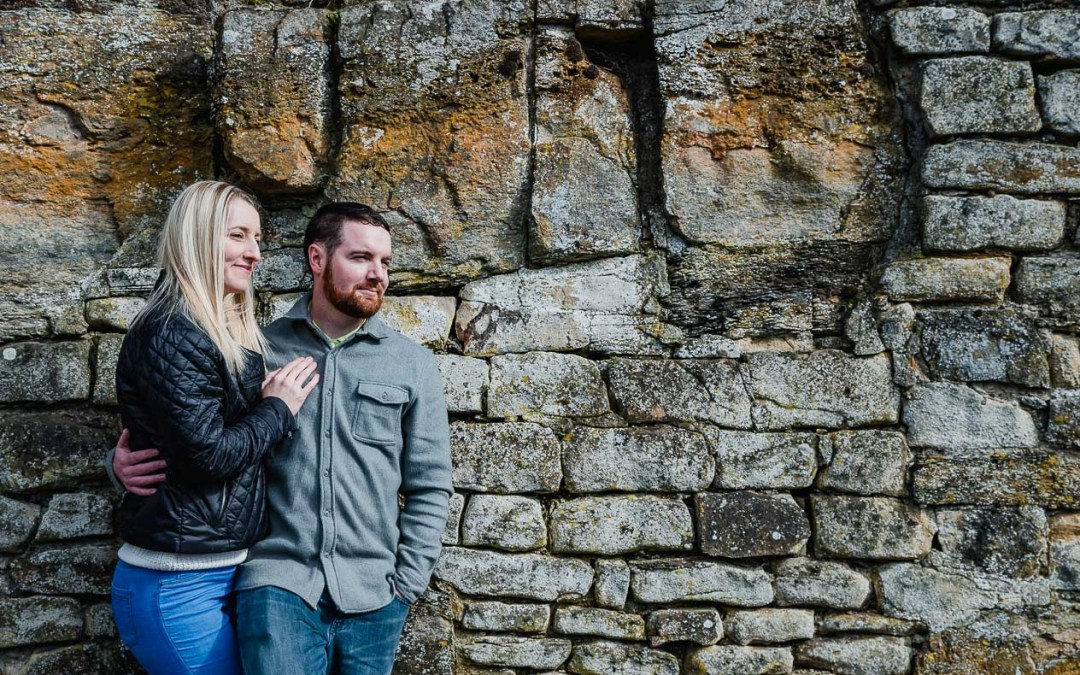 The engaged couple hug whilst looking out across the castle ruins during our North East lifestyle portrait engagement photography shoot at Barnard Castle, Teesdale, County Durham