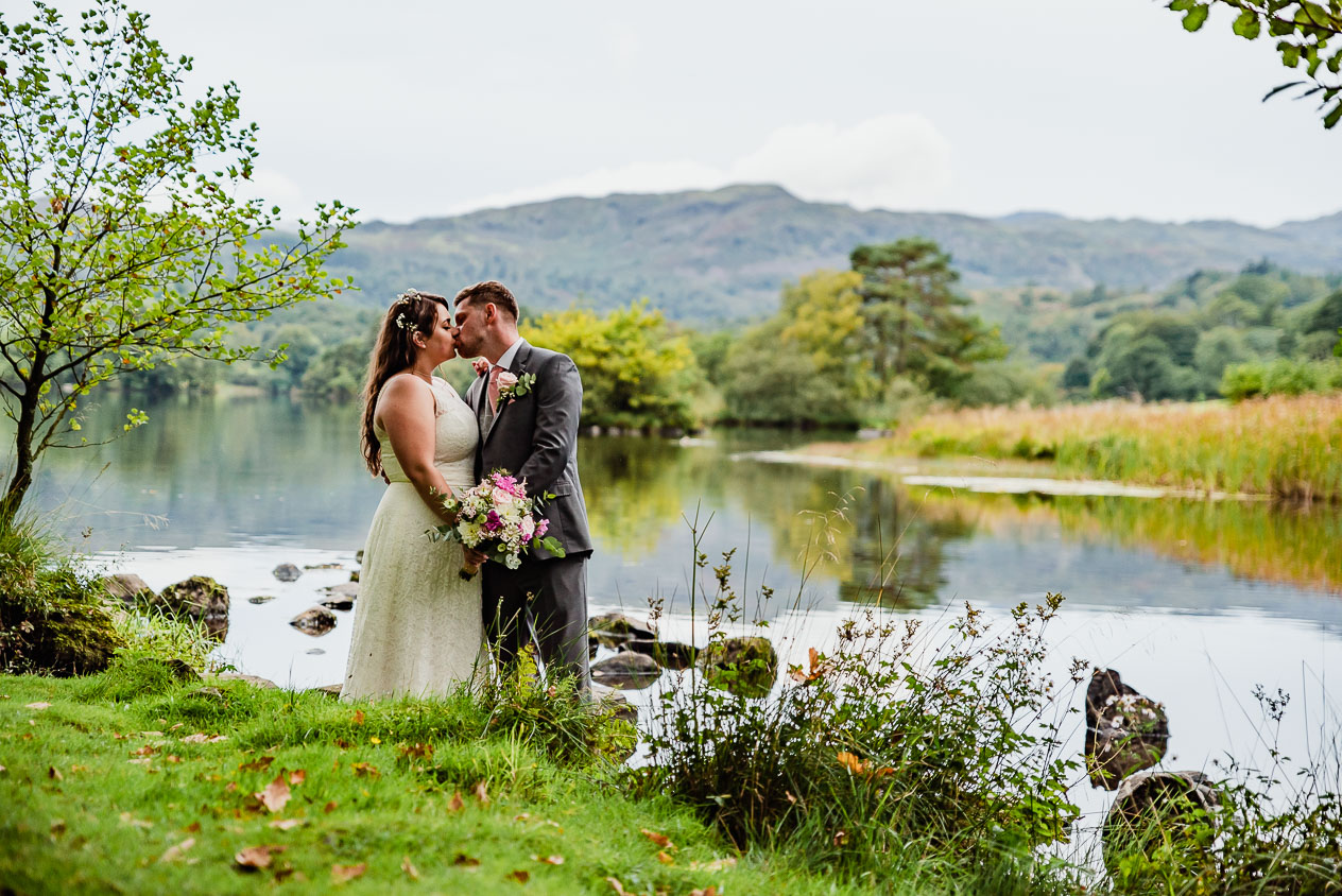 The couple kiss, showing the bouquet to the camera during Cote How Wedding taken by Lake District Wedding and Engagement Photographer, Cumbria