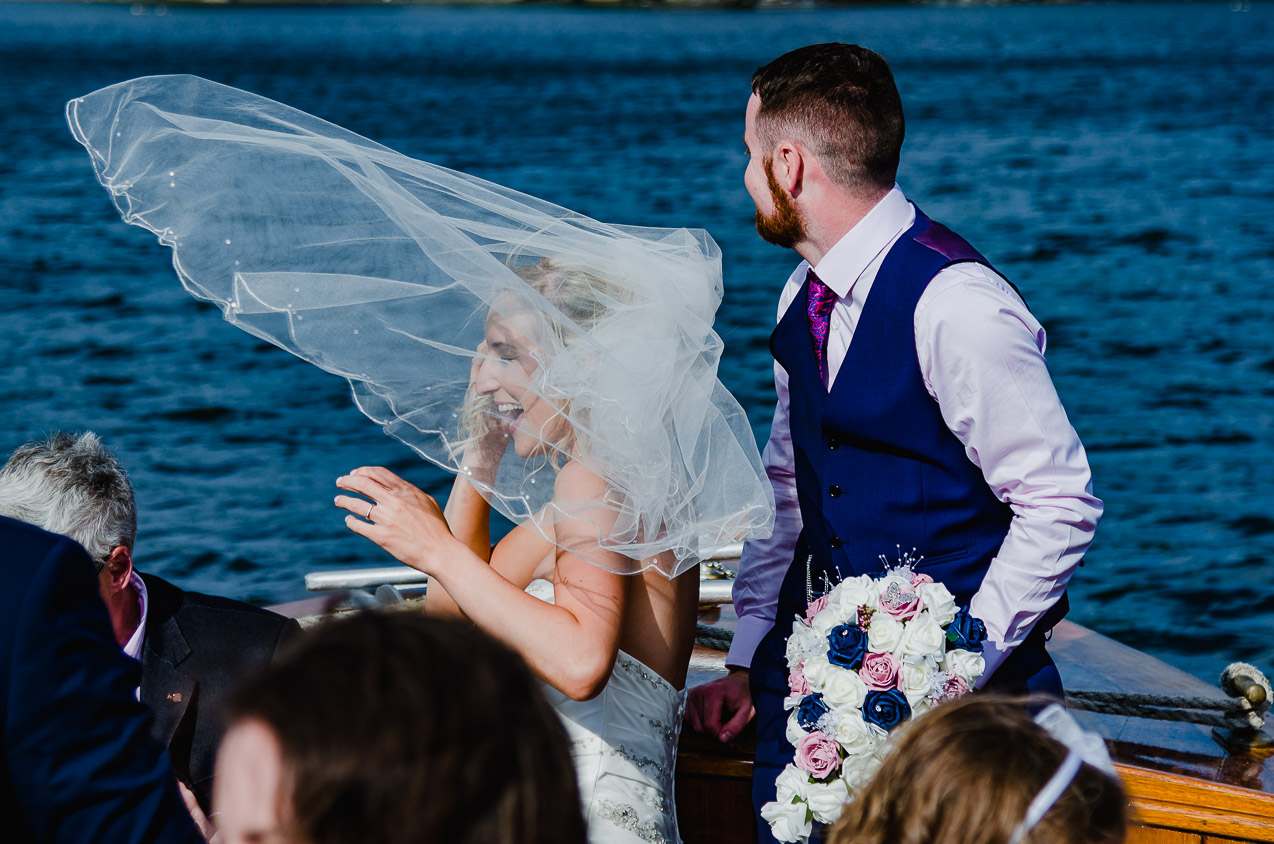 The wind catches the bride's veil and blows it across her face on the Derwentwater Keswick Launch boat during Skiddaw Hotel, Keswick wedding photography by lake district wedding photographer, Cumbria