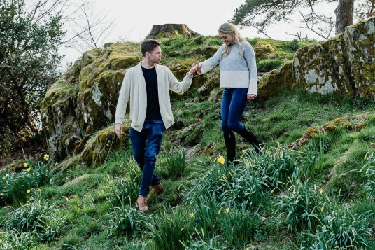 He helps her down the rock bank between the daffodils
