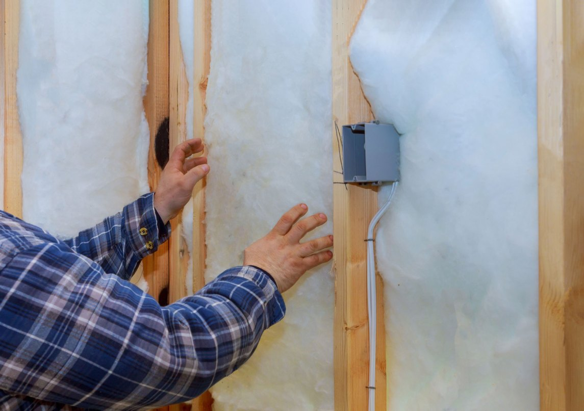 man installing batt fiberglass insulation