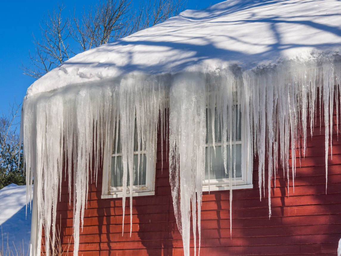 icicles on the eave of a red house