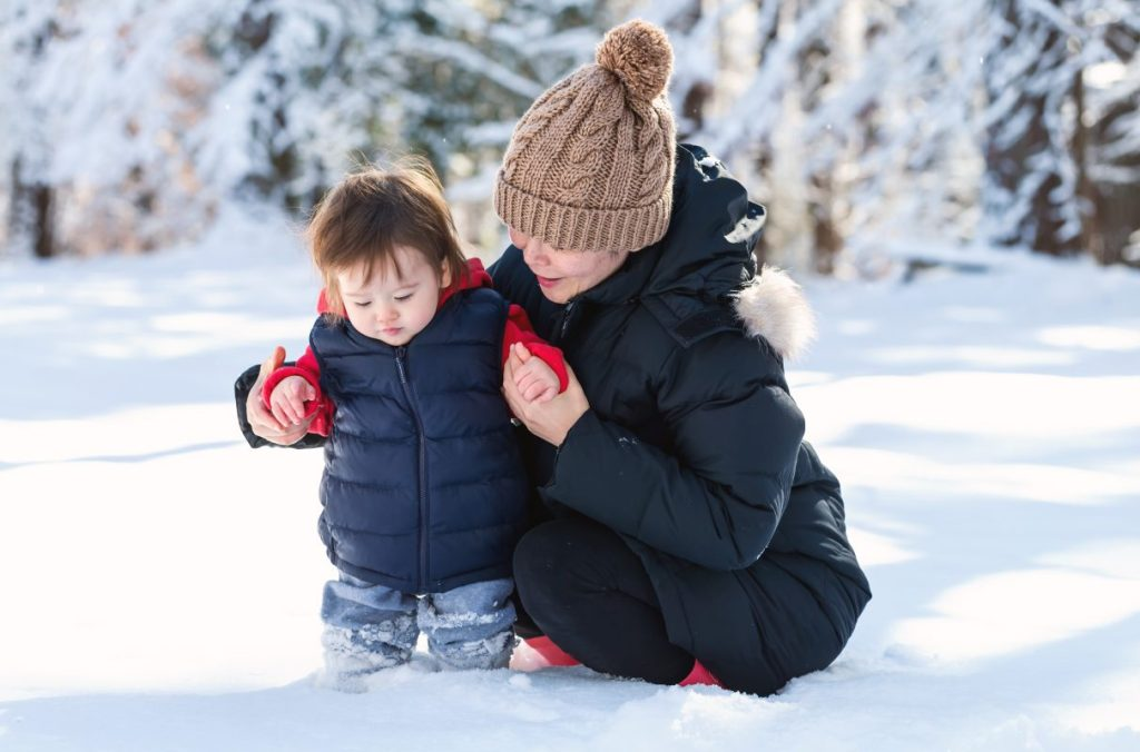 Toddler playing in snow with his mother. Children's diets need lots of nutrients in the winter.